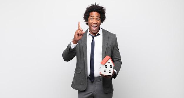 Giovane uomo afro nero che si sente come un genio felice ed eccitato dopo aver realizzato un'idea, alzando allegramente il dito, eureka!