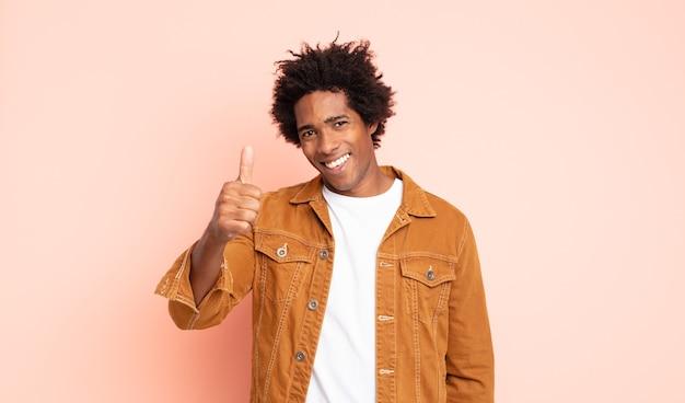 Giovane uomo afro nero che si sente orgoglioso, spensierato, fiducioso e felice, sorridendo positivamente con i pollici in su