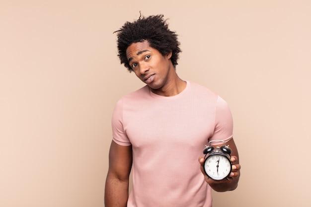 Giovane uomo afro nero che si sente perplesso e confuso, con un'espressione stupita e sbalordita guardando qualcosa di inaspettato