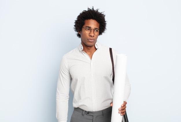 Giovane uomo afro nero che si sente triste, sconvolto o arrabbiato e guarda di lato con un atteggiamento negativo, accigliato in disaccordo