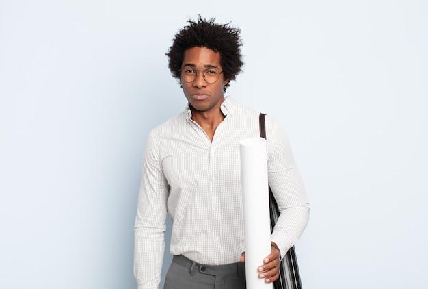 Giovane uomo afro nero che si sente triste e piagnucoloso con uno sguardo infelice, piange con un atteggiamento negativo e frustrato