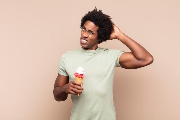 Giovane uomo afro nero che si sente stressato, preoccupato, ansioso o spaventato, con le mani sulla testa, in preda al panico per errore