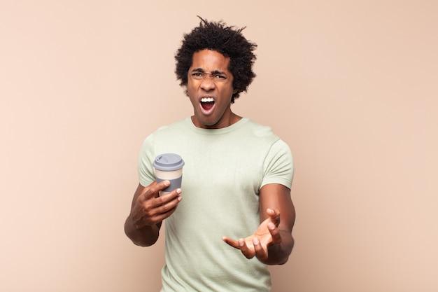 Giovane uomo afro nero che sembra arrabbiato, infastidito e frustrato urlando o cosa c'è di sbagliato in te