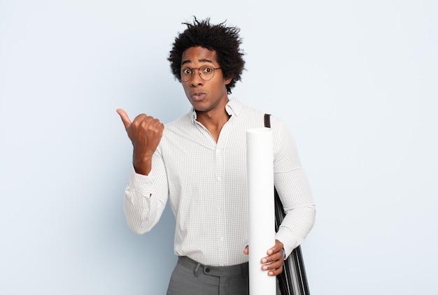 Giovane uomo afro nero che guarda stupito incredulo, indicando un oggetto sul lato e dicendo wow, incredibile