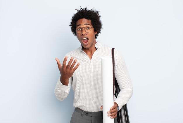 Giovane uomo afro nero che sembra disperato e frustrato, stressato, infelice e infastidito, gridando e urlando