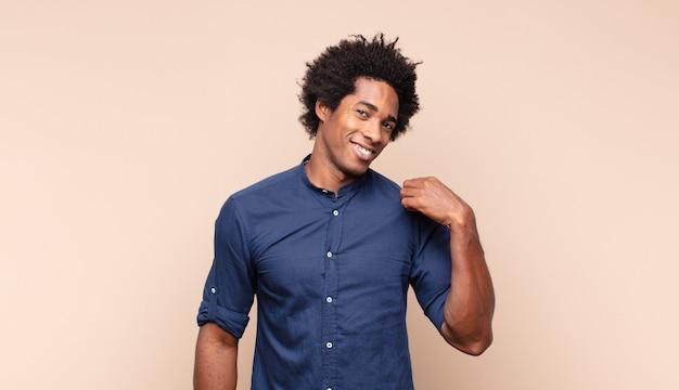 Giovane uomo afro nero che sembra eccitato e sorpreso che punta di lato e verso l'alto per copiare lo spazio