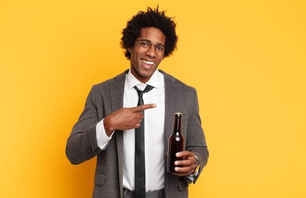 Giovane uomo afro nero che sembra eccitato e sorpreso che punta di lato e verso l'alto