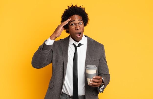 Giovane uomo afro nero che sembra felice, stupito e sorpreso, sorridente e realizzando incredibili e incredibili buone notizie
