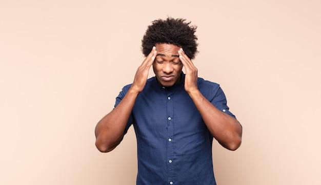 Giovane uomo afro nero che sembra felice, spensierato, amichevole e rilassato godersi la vita e il successo, con un atteggiamento positivo