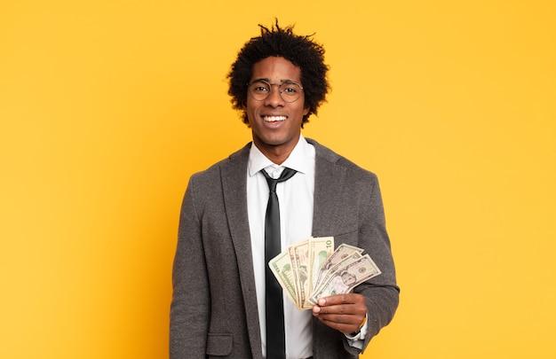 Giovane uomo afro nero che sembra felice e piacevolmente sorpreso, eccitato da un'espressione affascinata e scioccata