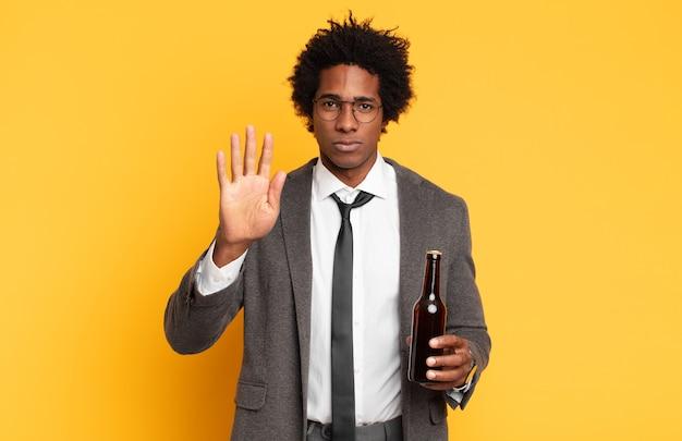 Giovane uomo afro nero che sembra serio, severo, dispiaciuto e arrabbiato che mostra il palmo aperto che fa il gesto di arresto
