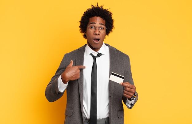 Giovane uomo afro nero che sembra scioccato e sorpreso con la bocca spalancata, indicando se stesso