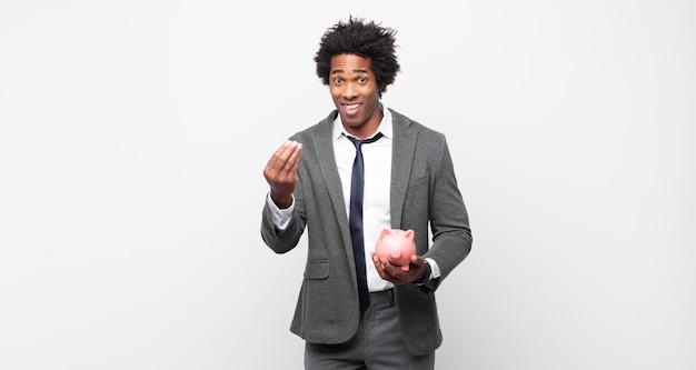 Giovane uomo afro nero che fa un gesto di denaro o di denaro, dicendoti di pagare i tuoi debiti!