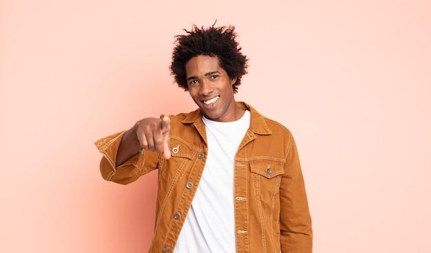 Giovane uomo afro nero che punta alla telecamera con un sorriso soddisfatto, fiducioso, amichevole, scegliendo te