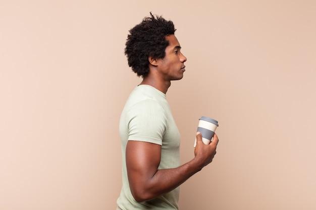 Giovane uomo afro nero sulla vista di profilo che cerca di copiare lo spazio davanti, pensare, immaginare o sognare ad occhi aperti