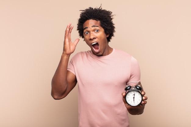 Giovane uomo afro nero che grida con le mani in aria, sentendosi furioso, frustrato, stressato e sconvolto