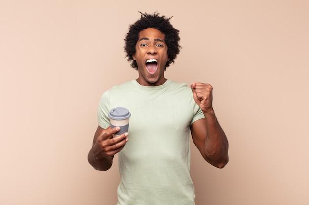 Giovane uomo afro nero che grida in modo aggressivo con un'espressione arrabbiata o con i pugni chiusi per celebrare il successo