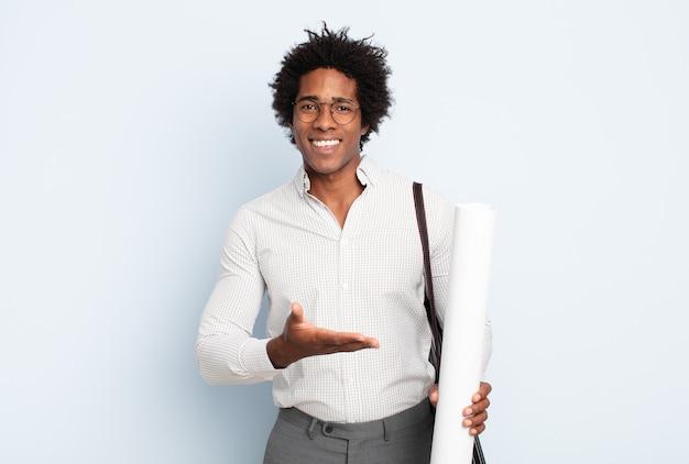 Giovane uomo afro nero che sorride allegramente, sentendosi felice e mostrando un concetto nello spazio della copia con il palmo della mano