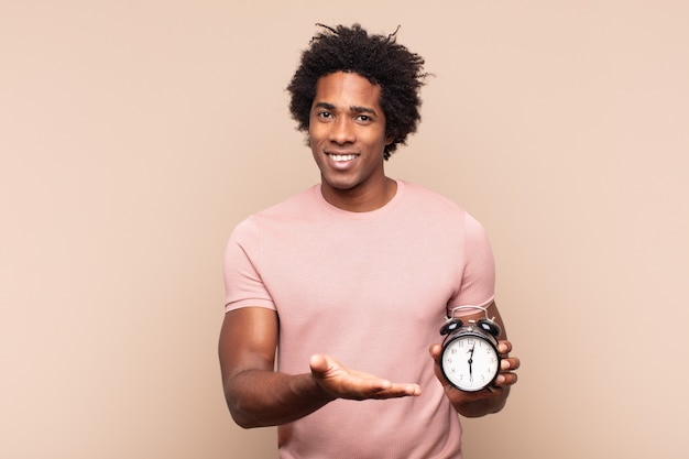 Giovane uomo afro nero che sorride allegramente, si sente felice e mostra un concetto nello spazio della copia con il palmo della mano