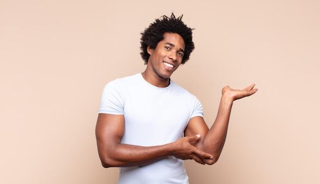 Giovane uomo afro nero che sorride allegramente dando un caldo, amichevole, amorevole abbraccio di benvenuto, sentendosi felice e adorabile