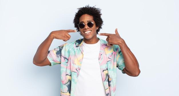 Giovane uomo afro nero che sorride fiduciosamente indicando il proprio ampio sorriso, atteggiamento positivo, rilassato e soddisfatto