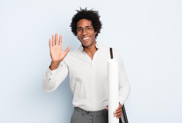 Giovane uomo afro nero che sorride allegramente e allegramente, agitando la mano, dandoti il benvenuto e salutandoti o salutandoti