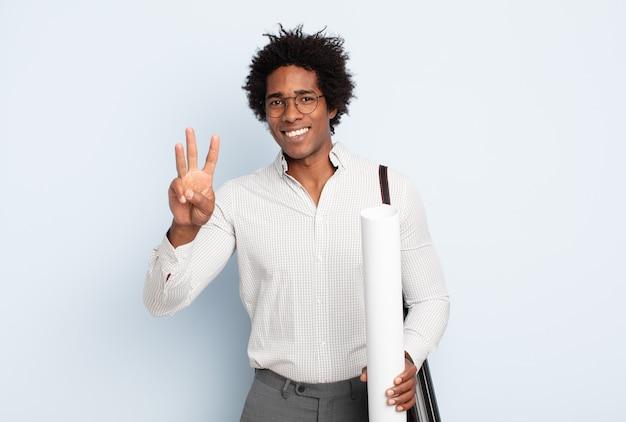 Giovane uomo afro nero sorridente e guardando amichevole, mostrando il numero tre o terzo con la mano in avanti, il conto alla rovescia