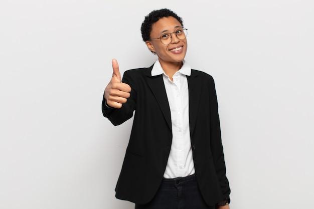 Giovane donna afro nera che si sente orgogliosa, spensierata, sicura e felice, sorridendo positivamente con i pollici in su