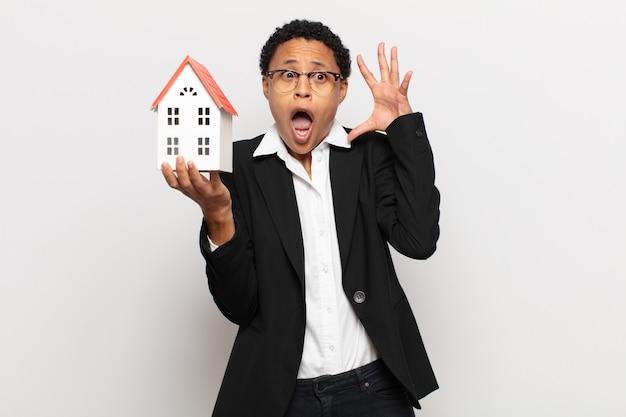 Giovane donna afro nera che grida con le mani in aria, sentendosi furiosa, frustrata, stressata e sconvolta
