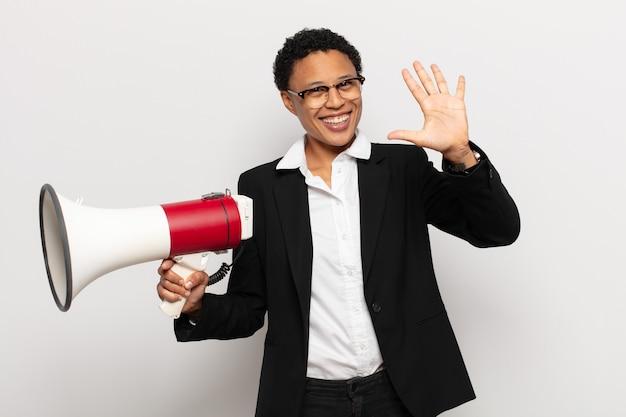 Giovane donna afro nera che sorride e sembra amichevole, mostrando il numero cinque o il quinto con la mano in avanti, conto alla rovescia
