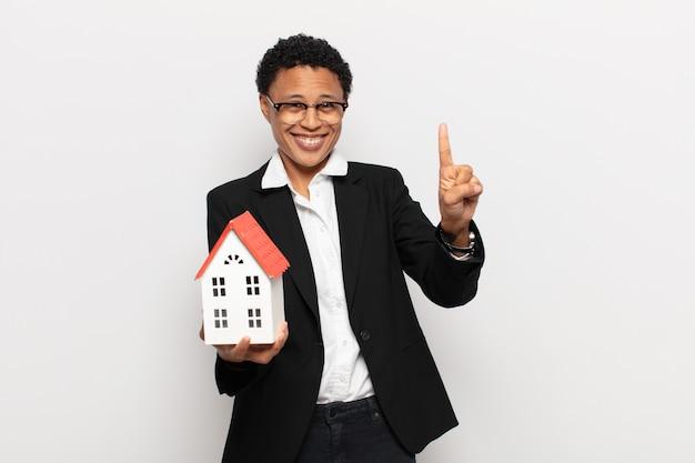 Giovane donna afro nera che sorride e sembra amichevole, mostrando il numero uno o il primo con la mano in avanti, il conto alla rovescia
