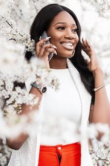 Giovane bella donna nera con un sorriso in piedi vicino a un albero in fiore con fiori e parlando al telefono cellulare. ragazza felice con uno smartphone in una calda giornata primaverile all'aperto