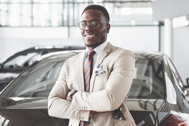 Giovane uomo d'affari nero sul salone automatico. concetto di vendita e noleggio auto.