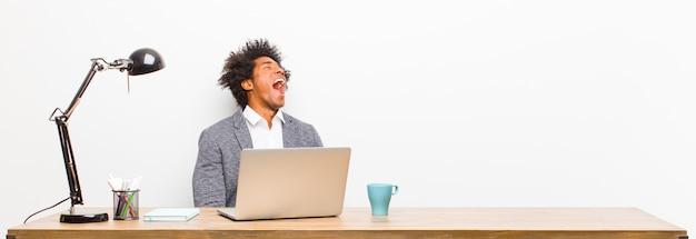 Giovane imprenditore nero urlando furiosamente, urlando in modo aggressivo, cercando stressato e arrabbiato su una scrivania