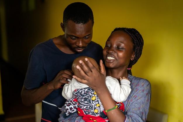 Giovane famiglia nera felice mamma e papà che tengono bambino
