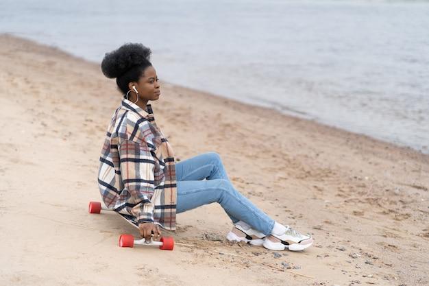 La giovane millenaria femmina nera si siede sulla spiaggia del fiume su longboard guardando l'acqua riflettendo pensando