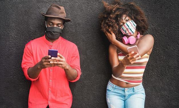 Giovani amici neri che usano il telefono cellulare mentre indossano una maschera protettiva per il viso durante l'epidemia di coronavirus - focus sui volti