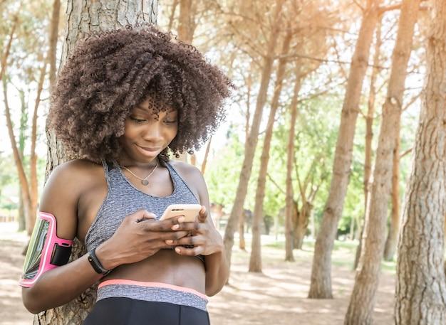 Giovane ragazza nera sorridente con capelli afro vestita per correre guardando lo smartphone in piedi appoggiato a un albero con alberi sullo sfondo in una foresta