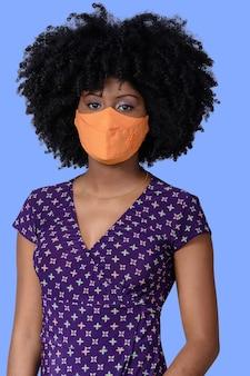 Giovane ragazza nera che indossa la maschera facciale isolata su sfondo blu