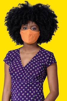 Giovane ragazza nera che indossa la maschera facciale isolata su sfondo giallo