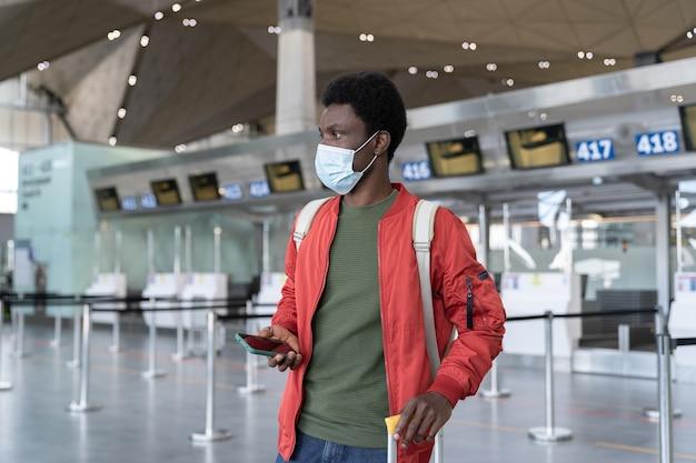 Il giovane viaggiatore maschio nero in aeroporto aspetta il volo usa la maschera per indossare lo smartphone nell'epidemia di covid
