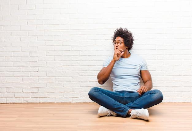 Giovane uomo di colore che chiede silenzio e tranquillità, gesticolando con un dito davanti alla bocca, dicendo shh o mantenendo un segreto seduto sul pavimento a casa