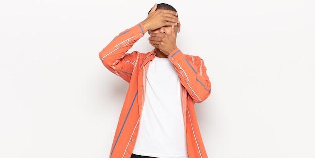 Giovane uomo di colore che copre il viso con entrambe le mani