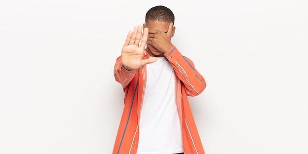 Giovane uomo di colore che copre il viso con la mano e mette l'altra mano davanti per fermare la fotocamera, rifiutando foto o immagini