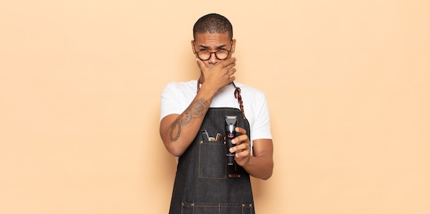 Giovane uomo di colore che copre la bocca con le mani con un'espressione scioccata e sorpresa, mantenendo un segreto o dicendo oops