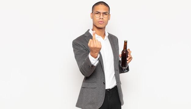 Giovane uomo di colore che si sente arrabbiato, infastidito, ribelle e aggressivo, lancia il dito medio, reagisce
