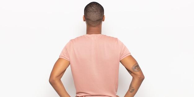 Giovane uomo di colore che si sente confuso o pieno o dubbi e domande, chiedendosi, con le mani sui fianchi, vista posteriore