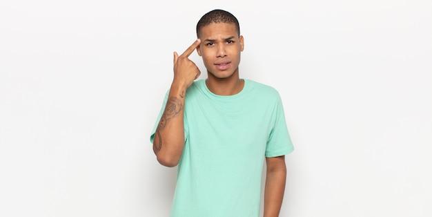 Giovane uomo di colore che si sente confuso e perplesso, dimostrando che sei pazzo, pazzo o fuori di testa