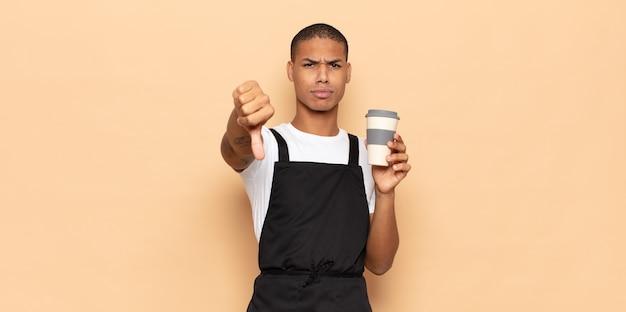 Giovane uomo di colore che si sente arrabbiato, arrabbiato, infastidito, deluso o scontento, mostrando i pollici verso il basso con uno sguardo serio