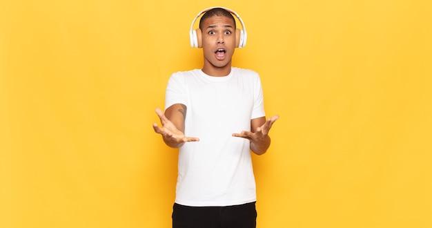 Giovane uomo di colore estremamente scioccato e sorpreso, ansioso e in preda al panico, con uno sguardo stressato e inorridito
